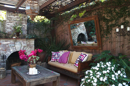 A beautiful wood framed mirror looks perfect in this cozy patio.