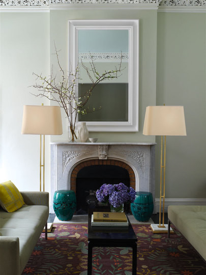 wall mirror in a simple yet classic white frame graces the mantel