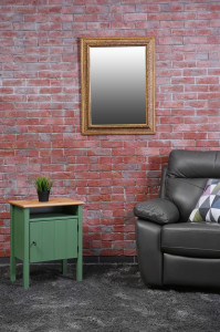 Brown leather armchair and green small table against brick wall background